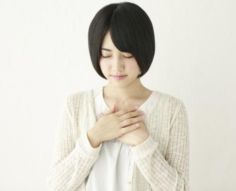 痛む胸を押さえる女性の写真